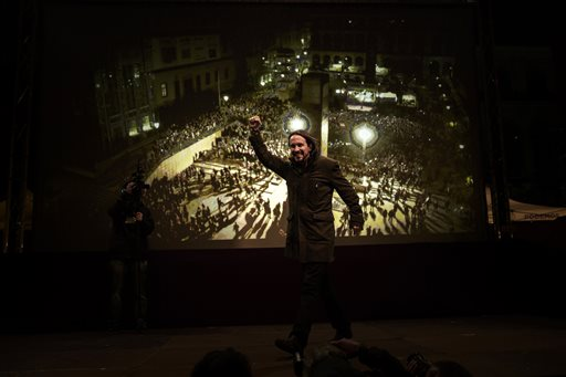 Podemos party leader Pablo Iglesias celebrates following the latest official election results in Madrid, Monday, Dec. 21, 2015. Podemos supporters gathered outside their party headquarters in Madrid cheering as general election results began to roll in confirming the newcomer on the political scene looked set to capture 68 seats and a chance of forming a coalition in parliament.(AP Photo/Daniel Ochoa de Olza)