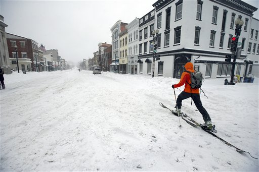 A man uses cross country skies as he goes down M Street NW in the snow, Saturday, Jan. 23, 2016 in the Georgetown area of Washington. A blizzard with hurricane-force winds brought much of the East Coast to a standstill Saturday, dumping as much as 3 feet of snow, stranding tens of thousands of travelers and shutting down the nation's capital and its largest city. (AP Photo/Alex Brandon)