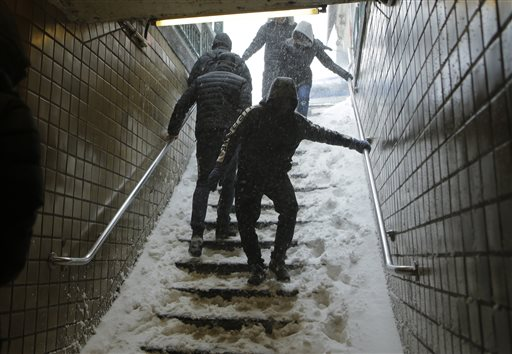 Travelers navigate snow covered steps at the Union Turnpike subway station in the Queens borough of New York during a snowstorm Saturday, Jan. 23, 2016. New York Gov. Andrew Cuomo has announced a travel ban in New York City and on Long Island, saying all non-emergency vehicles should be off New York City's roads after 2:30 p.m. Saturday. (AP Photo/Frank Franklin II)