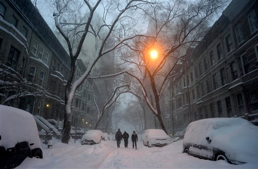 Pedestrians walk in New York, Saturday, Jan. 23, 2016. A massive winter storm buried much of the U.S. East Coast in a foot or more of snow by Saturday, shutting down transit in major cities, stranding drivers on snowbound highways, knocking out power to tens of thousands of people. (AP Photo/Craig Ruttle)