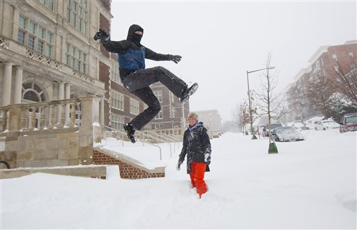 Ian Wright, left, leaps into a snow bank as his wife Rebecca, center, watches on their street in the Columbia Heights neighborhood of in Washington, Saturday, Jan. 23, 2016. Millions of people awoke Saturday to heavy snow outside their doorsteps, strong winds that threatened to increase through the weekend, and largely empty roads as residents from the South to the Northeast heeded warnings to hunker down inside while a mammoth storm barreled across a large swath of the country. (AP Photo/Pablo Martinez Monsivais)