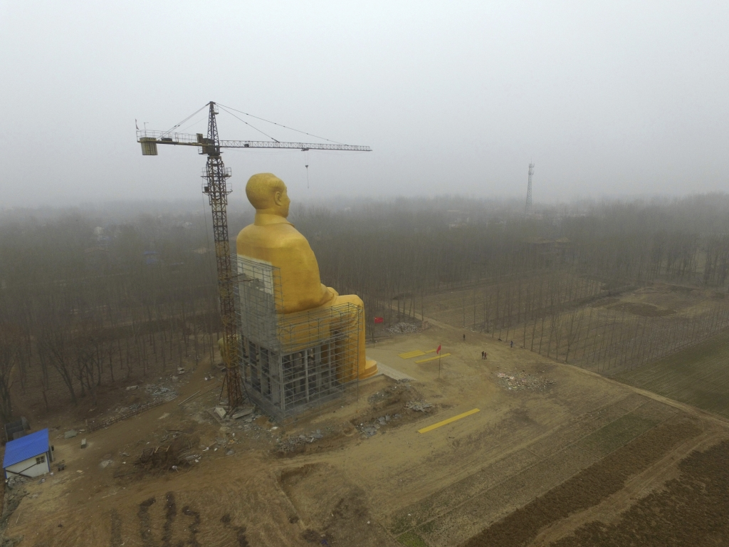 In this Monday, Jan. 4, 2016 photo, a construction crane rises next to a 36.6-meter (120-foot) tall gold-colored statue of former Chinese leader Mao Zedong in Tongxu County in central China's Henan province. According to Chinese state media, businessmen and local villagers contributed nearly 3 million yuan ($457,000) to build the cement statue. (Chinatopix via AP) CHINA OUT