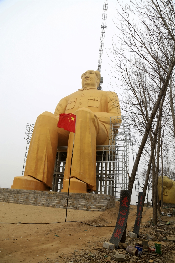 In this Monday, Jan. 4, 2016 photo, a Chinese flag flies next to a 36.6-meter (120-foot) tall gold-colored statue of former Chinese leader Mao Zedong in Tongxu County in central China's Henan province. According to Chinese state media, businessmen and local villagers contributed nearly 3 million yuan ($457,000) to build the cement statue. (Chinatopix via AP) CHINA OUT