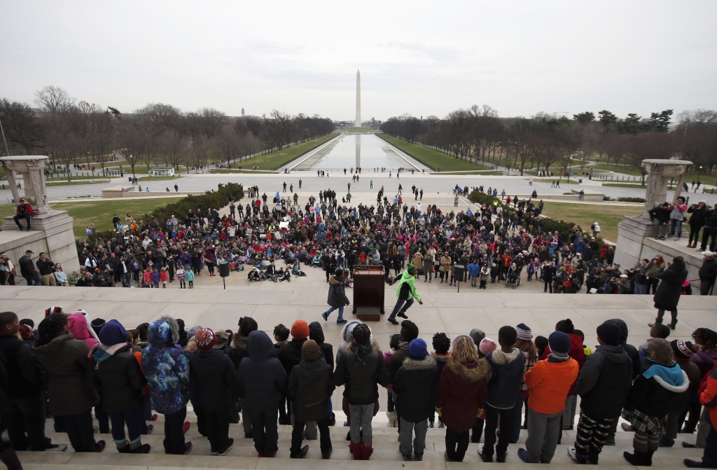 """Fifth-graders from Watkins Elementary School in Washington, stand as they wait their turn to recite a line from Martin Luther King, Jr.'s 1963 """"I Have a Dream,"""" speech during a program on the steps of the Lincoln Memorial, looking toward the Washington Monument in Washington, Friday, Jan. 15, 2016. The students recited the speech and sang a song in honor of his upcoming birthday. (AP Photo/Alex Brandon)"""