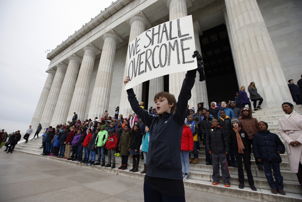 """Doug Bradshaw, 11, a fifth-grader from Watkins Elementary School in Washington, holds a sign during a program on the steps of the Lincoln Memorial in Washington, Friday, Jan. 15, 2016, where students recited Martin Luther King, Jr.'s 1963 """"I Have a Dream,"""" speech and sang a song, in honor of his upcoming birthday. (AP Photo/Alex Brandon)"""