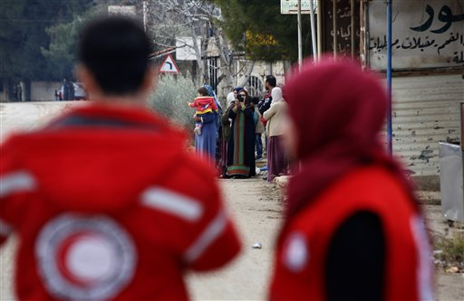 In this Monday, Jan. 11, 2016 photo, members of the Syrian Red Cross stand near aid vehicles loaded with food and other supplies that entered the besieged town of Madaya about 15 miles (24 kilometers) northwest of Damascus, Syria. Madaya has been blockaded for months by government troops and the Lebanese militant group Hezbollah. Opposition activists and aid groups have reported several deaths from starvation in recent weeks. (AP Photo)