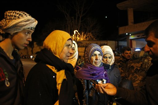 In this Monday, Jan. 11, 2016 photo, residents talk to a reporter after the arrival of an aid convoy, in the besieged town of Madaya, northwest of Damascus, Syria. Aid convoys reached three besieged villages on Monday — Madaya, near Damascus, where U.N. humanitarian chief Stephen O'Brien said about 400 people need to be evacuated immediately to receive life-saving treatment for medical conditions, malnourishment and starvation, and the Shiite villages of Foua and Kfarya in northern Syria. Reports of starvation and images of emaciated children have raised global concerns and underscored the urgency for new peace talks that the U.N. is hoping to host in Geneva on Jan. 25. (AP Photo)