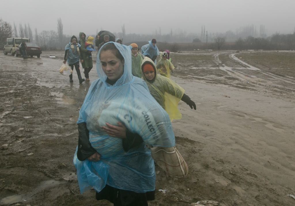 A migrant mother carries her baby covered with a plastic sheet as they walk from the Macedonian border into Serbia, near the village of Miratovac, Serbia, Wednesday, Jan. 6, 2016. Hundreds of migrants continue to arrive daily into Serbia in order to register and continue their journey further north towards Western Europe. (AP Photo/Visar Kryeziu)