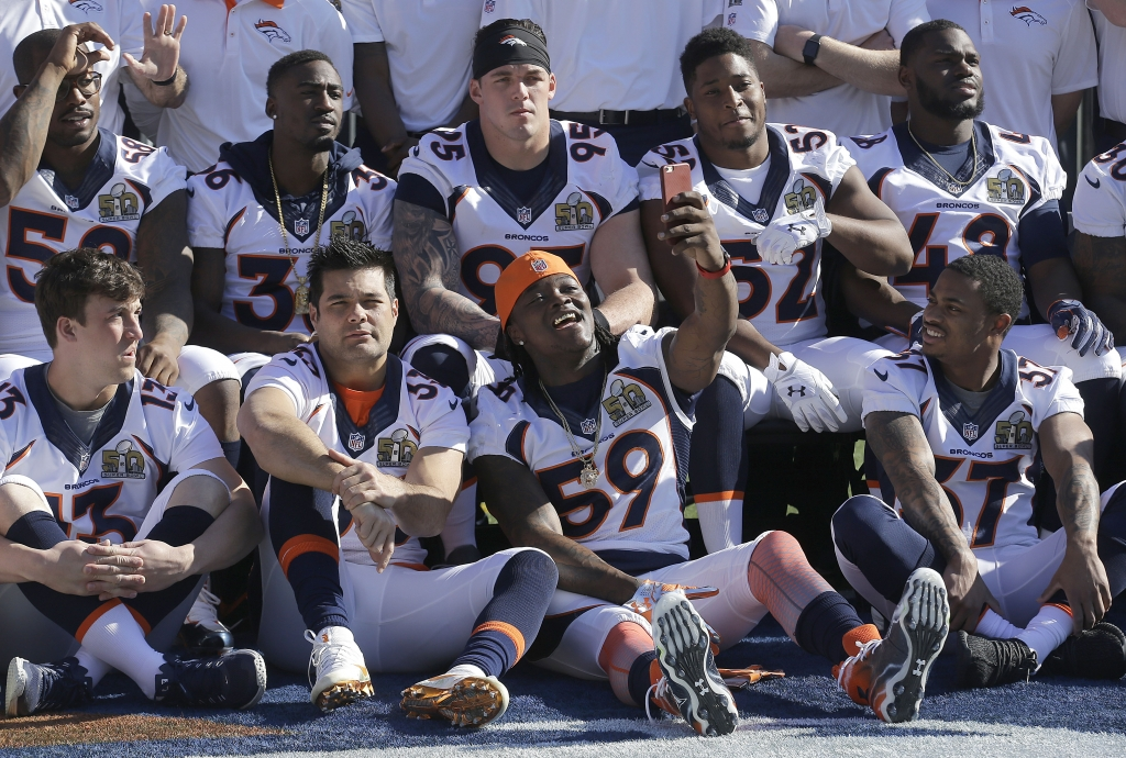 Denver Broncos linebacker Danny Trevathan (59) holds up his phone as he poses with teammates for photos before an NFL football walk through practice in Santa Clara, Calif., Saturday, Feb. 6, 2016. (AP Photo/Jeff Chiu)