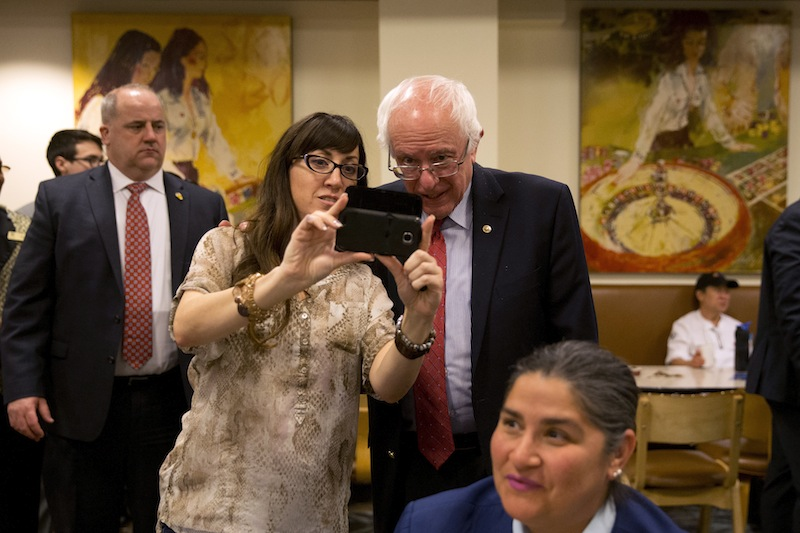 Democratic presidential candidate Sen. Bernie Sanders, I-Vt., pauses for a selfie as he greets hotel workers at Caesars Palace hotel and casino Friday, Feb. 19, 2016, in Las Vegas. (AP Photo/Jae C. Hong)