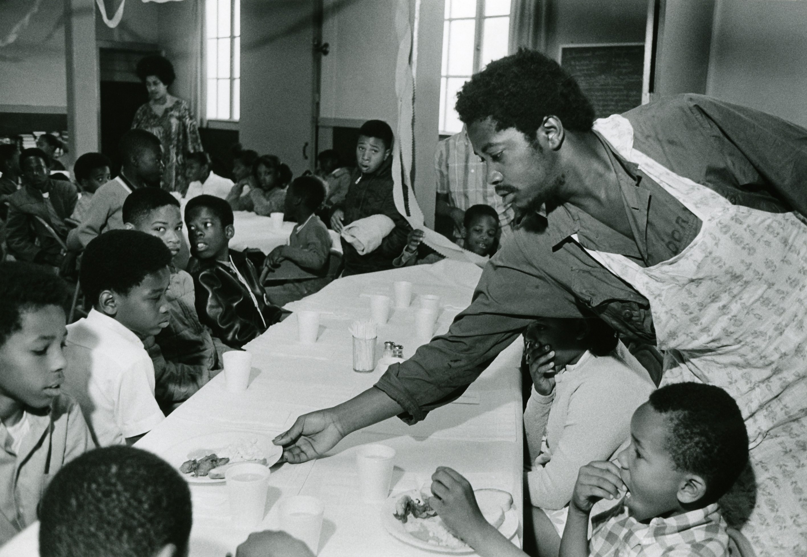 black panthers dogwoof document#2 Charles Bursey hands plate of food to a child seated at Free Breakfast Program. Photo courtesy of Pirkle Jones and Ruth-Marion Baruch.PJ_v1