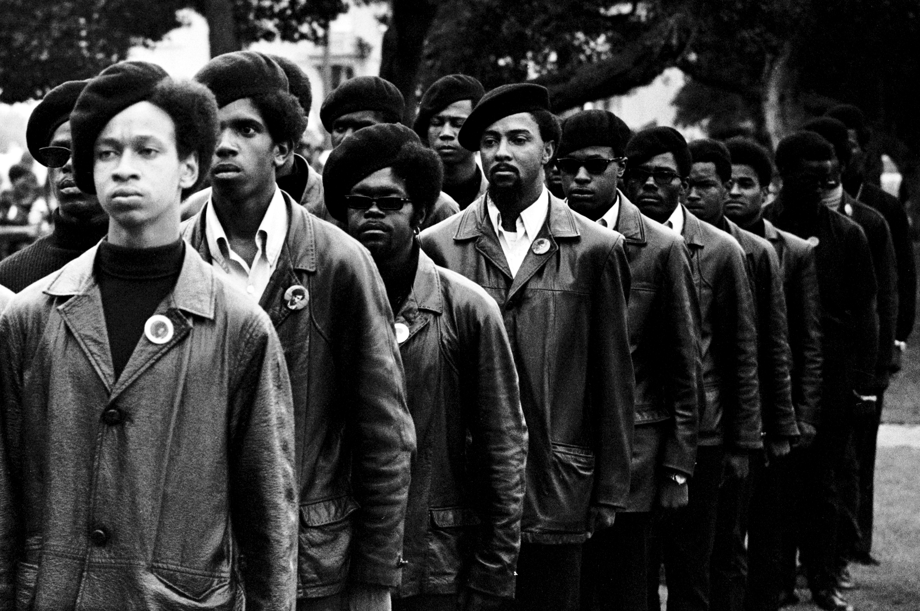 Panthers line up at a Free Huey rally in Defermery Park, in west Oakland's ghetto. Light skinned man is Gregory Harrison. His brother, Oleander, went to Sacramento with Bobby & Huey. July 28, 1968