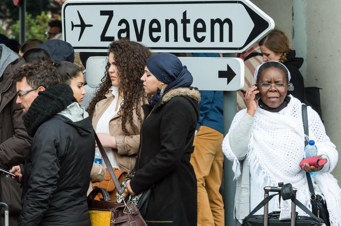 People stand near Brussels airport after being evacuated following explosions that rocked the facility in Brussels, Belgium, Tuesday March 22, 2016. Authorities locked down the Belgian capital on Tuesday after explosions rocked the Brussels airport and subway system, killing a number of people and injuring many more. Belgium raised its terror alert to its highest level, diverting arriving planes and trains and ordering people to stay where they were. Airports across Europe tightened security. (ANSA/AP Photo/Geert Vanden Wijngaert)