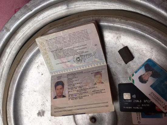 In this photo released by the Egyptian Ministry of Interior on Thursday, Mar. 24, 2016, personal belongings of slain Italian graduate student Giulio Regeni, including his passport, are displayed. Egypt's Interior Ministry said Thursday it has killed members of a gang suspected of being linked to the killing Regini student whose torture and death sparked an international outcry over possible involvement of Egyptian police in his brutal killing. The ministry said that police raided one of the men's houses and found the personal belongings of Regeni, including his red handbag bearing the picture of the Italian flag, his passport and other identification cards, including one belonging to Cambridge University, in addition to his cellphones. (Egyptian Interior Ministry via AP)