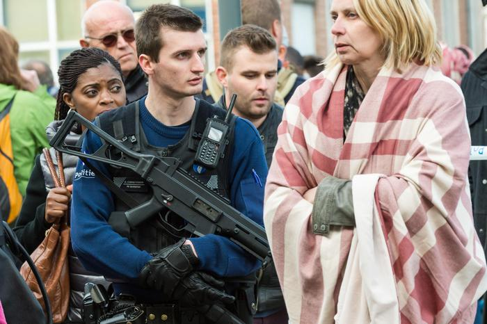 A police officer stands guard as people are evacuated from Brussels airport, after explosions rocked the facility in Brussels, Belgium, Tuesday March 22, 2016. Authorities locked down the Belgian capital on Tuesday after explosions rocked the Brussels airport and subway system, killing a number of people and injuring many more. Belgium raised its terror alert to its highest level, diverting arriving planes and trains and ordering people to stay where they were. Airports across Europe tightened security. (ANSA/AP Photo/Geert Vanden Wijngaert)