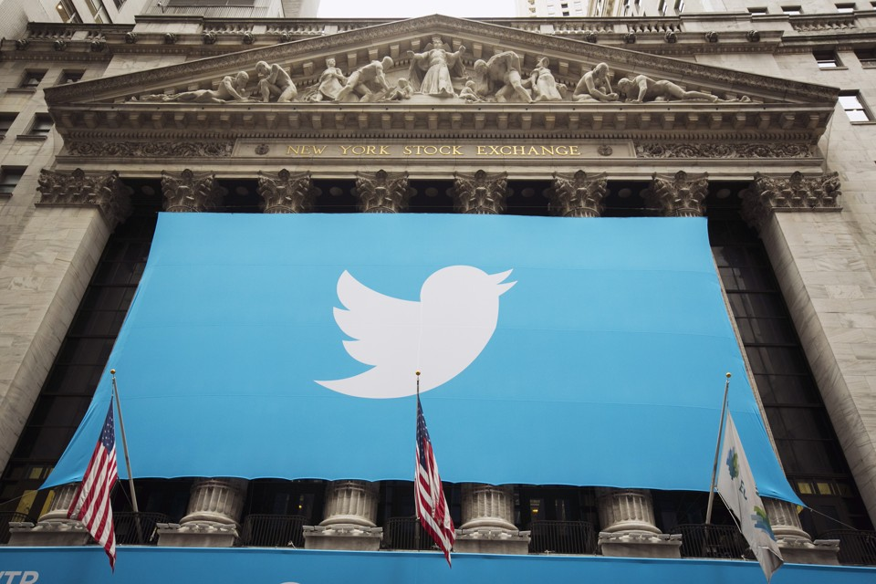 A sign displays the Twitter logo on the front of the New York Stock Exchange ahead of the company's IPO in New York, November 7, 2013. Twitter Inc could face volatile trade in its debut Thursday on the New York Stock Exchange, analysts said, but they remained enthusiastic after the money-losing social media company priced its IPO above the expected range. The microblogging network priced 70 million shares at $26 on Wednesday evening, above the targeted range of $23 to $25, which had been raised once before. The IPO values Twitter at $14.1 billion (8.8 billion pounds), with the potential to reach $14.4 billion if underwriters exercise an over-allotment option. REUTERS/Lucas Jackson (UNITED STATES - Tags: BUSINESS SCIENCE TECHNOLOGY) - RTX153RU