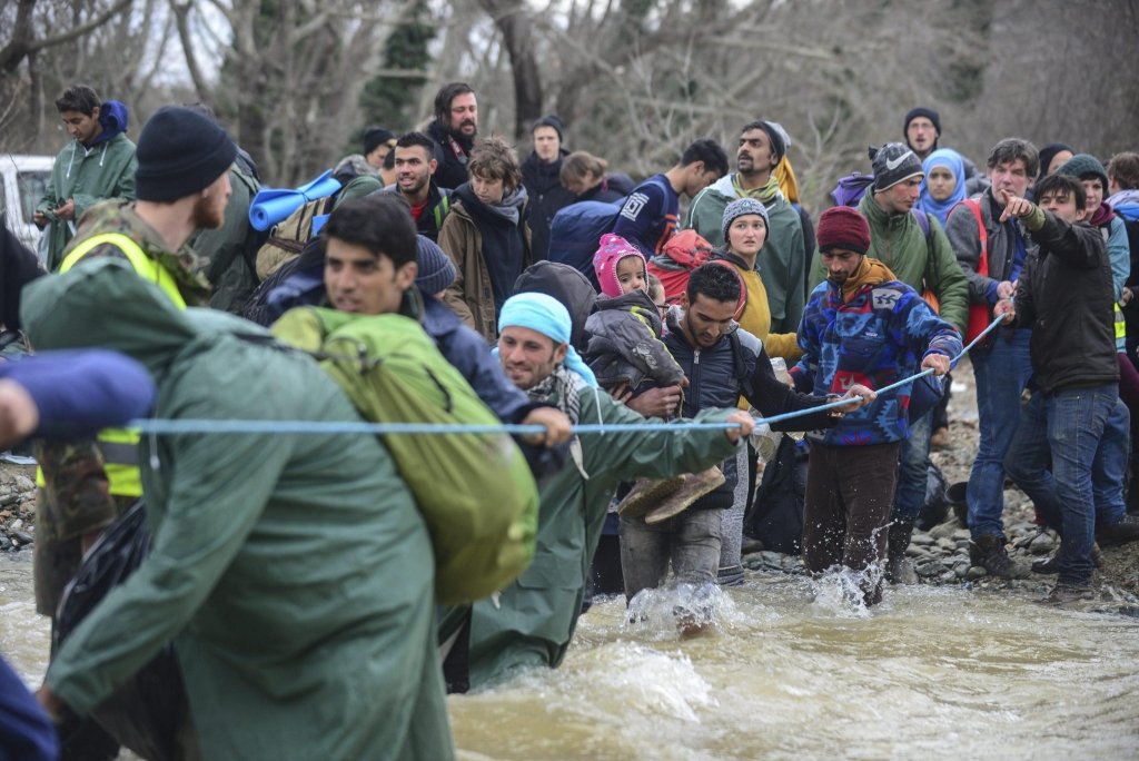 epaselect epa05211159 Migrants from a camp near Idomeni village, cross the river trying to find alternative way to cross the Greek-Macedonian border, near Idomeni, northern Greece, 14 March 2016. Greece has registered in its territory more of 44,000 migrants trapped due to entry restrictions already imposed by Macedonia in recent months, by denying entry to all those who are considered economic migrants, prohibiting the passage of Afghans, and finally denying entry to all Syrians and Iraqis who are not from combat areas. EPA/NAKE BATEV