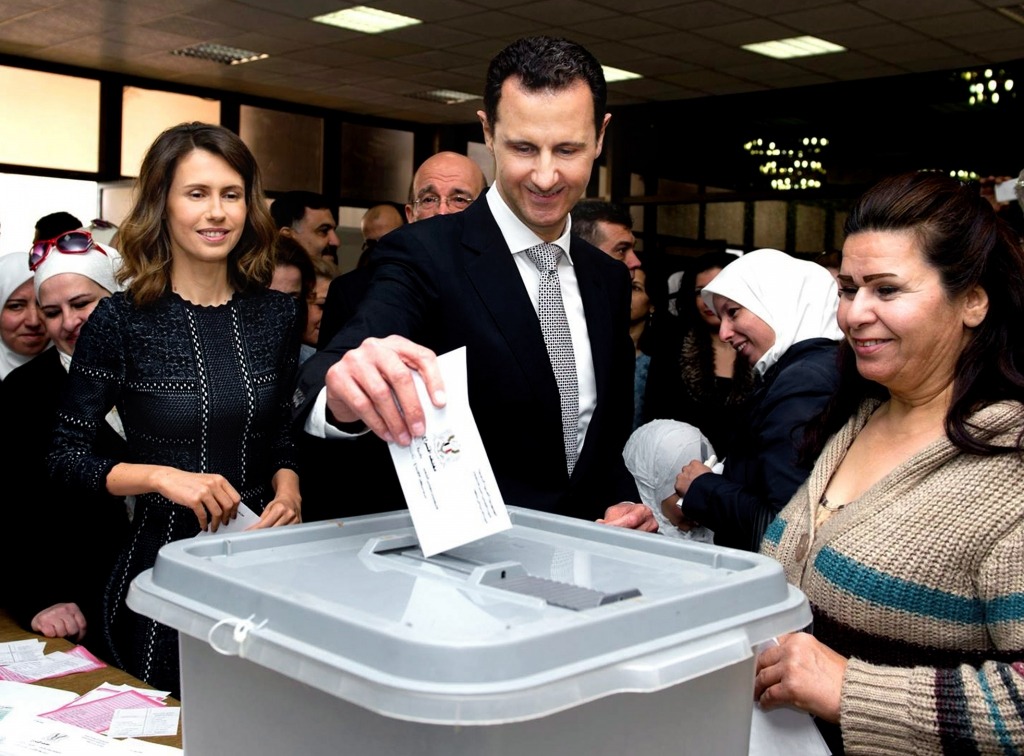 This photo released on the official Facebook page of Syrian Presidency, shows Syrian President Bashar Assad casting his ballot in the parliamentary elections, as his wife Asma, left, is standing next to him, in Damascus, Syria, Wednesday, April 13, 2016. Syrians living in government-held areas are to vote Wednesday in parliamentary elections, hours ahead of the resumption of talks in Geneva to resolve the country's five-year-long civil war. (Syrian Presidency via AP)