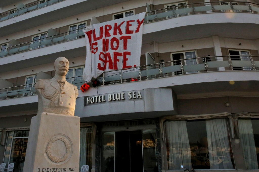 epa05243083 A banner reading: 'Turkey is not Safe' hangs from a hotel as migrants are escorted by FRONTEX officers to ferries in the port of Mytilene, Lesvos island, Greece, early 04 April 2016. Some 160 migrants, from Pakistan, Bangladesh and Morroco, who refused to apply for asylum, have been deported on early morning 04 April to Turkey, after an agreement between the European Union (EU) and Turkey on the refugees crisis. EPA/ORESTIS PANAGIOTOU