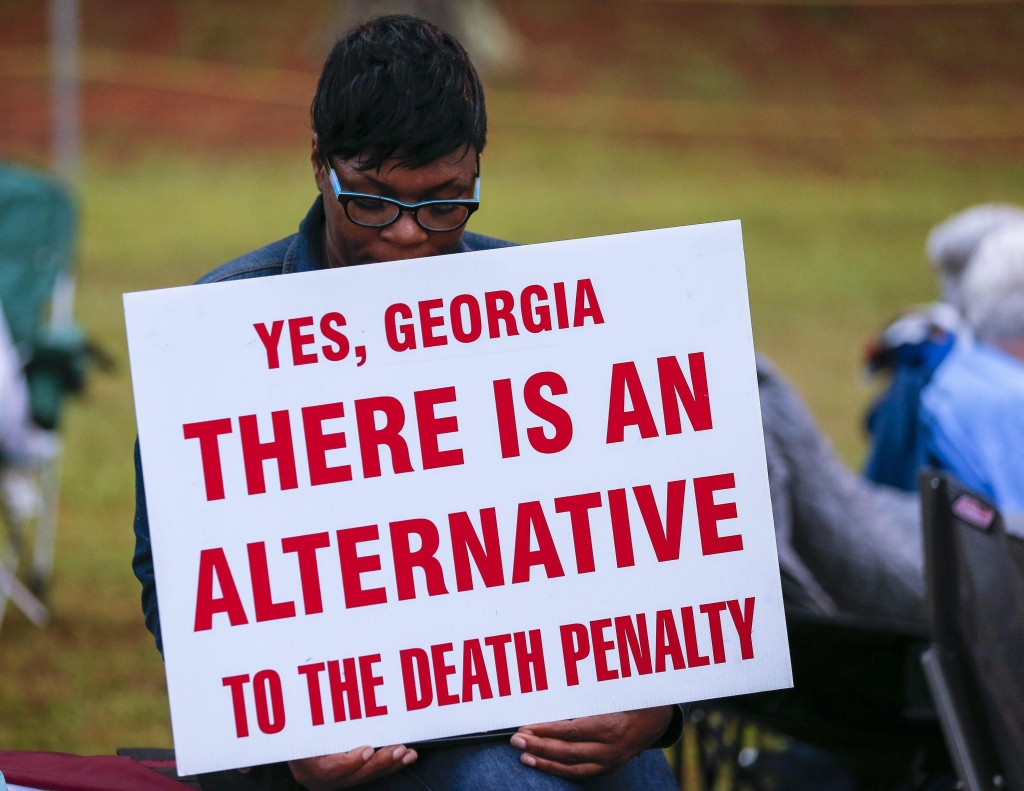epa04956658 An anti death penalty protester holds a sign outside the Georgia Diagnostic Prison before the scheduled execution by lethal injection of Kelly Gissendaner in Jackson Georgia, USA, 29 September 2015. Gissendaner, convicted of plotting to kill her husband, would be the first woman executed in Georgia in 70 years. EPA/ERIK S. LESSER