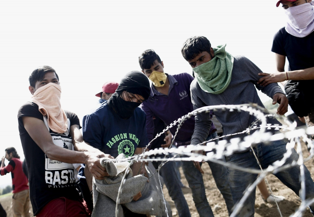 epa05256869 Refugees pull barbed wire fence during a protest demanding the opening of the borders, at the refugee camp in Idomeni, on the border between Greece and the Former Yugoslav Republic of Macedonia (FYROM), 13 April 2016. Two Greek police squads were deployed along the fence in the buffer zone at Idomeni in an attempt to prevent refugees to reach the fence. Currently an estimate 100 refugees are scattered in the fields next to the fence. A few days earlier Macedonian police had thrown tear gas at refugees trying to tear down the fence and get into FYROM.  EPA/KOSTAS TSIRONIS