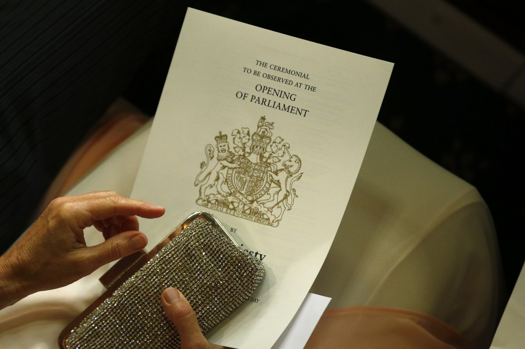 A guest of a member of the House of Lords holds her program ahead of Britain's Queen Elizabeth II reading the Queen's Speech during the State Opening of Parliament in the House of Lords in London, Wednesday, May, 18, 2016. The State Opening of Parliament marks the formal start of the parliamentary year and the Queen's Speech sets out the government's agenda for the coming session.(AP Photo/Alastair Grant Pool)