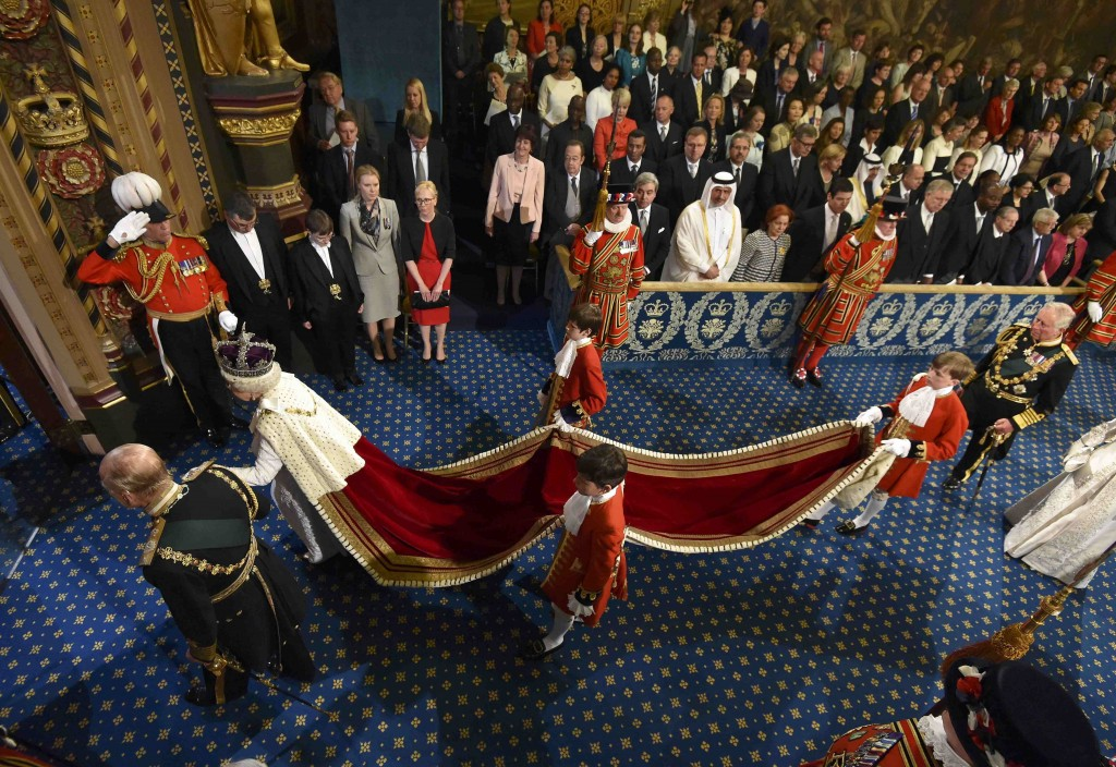 Britain's Queen Elizabeth II holds the hand of Prince Philip, as they proceed through the Royal Gallery for the State Opening of Parliament in the House of Lords, at the Palace of Westminster in London, Wednesday May 18, 2016. The Queen will give a speech to parliament about the government's programme for the upcoming parliamentary year. Prince Charles follows, right, (Toby Melville / Pool via AP)