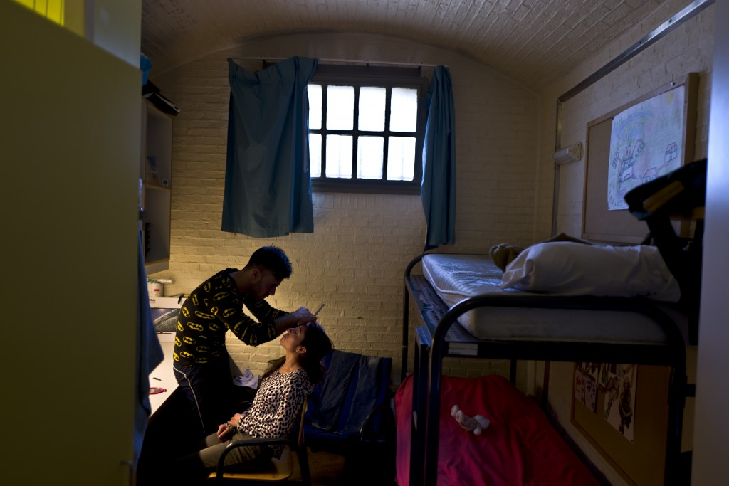 In this Sunday, May 1, 2016 photo, Yazidi refugee Yassir Hajji, 24, from Sinjar, Iraq, adjusts the eyebrow of his wife Gerbia,18, at their room in the former prison of De Koepel in Haarlem, Netherlands. (AP Photo/Muhammed Muheisen)