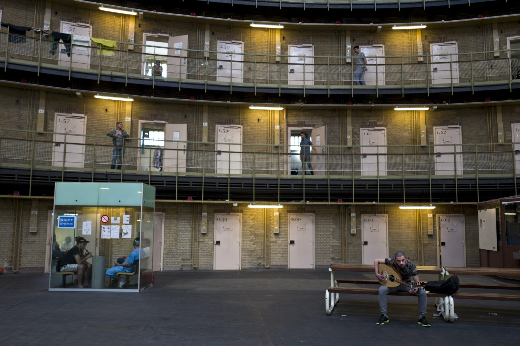 In this Thursday, April 21, 2016 photo, Syrian refugee Fadi Tahhan, 23, right, sings while playing Oud at the former prison of De Koepel in Haarlem, Netherlands. With crime declining in the Netherlands, the country is looking at new ways to fill its prisons. (AP Photo/Muhammed Muheisen)