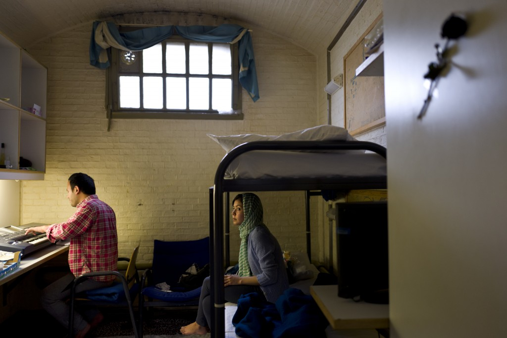 In this Wednesday, April 6, 2016 photo, Afghan refugee Hamed Karmi, 27, plays keyboard next to his wife Farishta Morahami, 25, sitting on a bed inside their room at the former prison of De Koepel in Haarlem, Netherlands. The government has let Belgium and Norway put prisoners in its empty cells and now, amid the huge flow of migrants into Europe, several Dutch prisons have been temporarily pressed into service as asylum seeker centers. (AP Photo/Muhammed Muheisen)