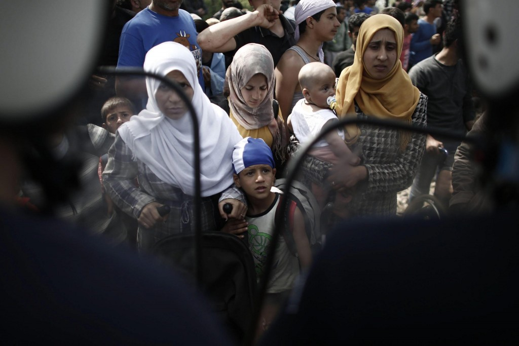 epa05248126 Refugee children along with their mothers stand in front of riot policemen during a protest demanding the opening of the borders at the border line between Greece and FYROM at the refugee camp of Idomeni, Greece, 07 April 2016. Migrants who refuse to apply for asylum are to be deported to Turkey, in accordance with a tit-for-tat agreement between the European Union (EU) and Turkey on the refugee and migration crisis. EPA/KOSTAS TSIRONIS
