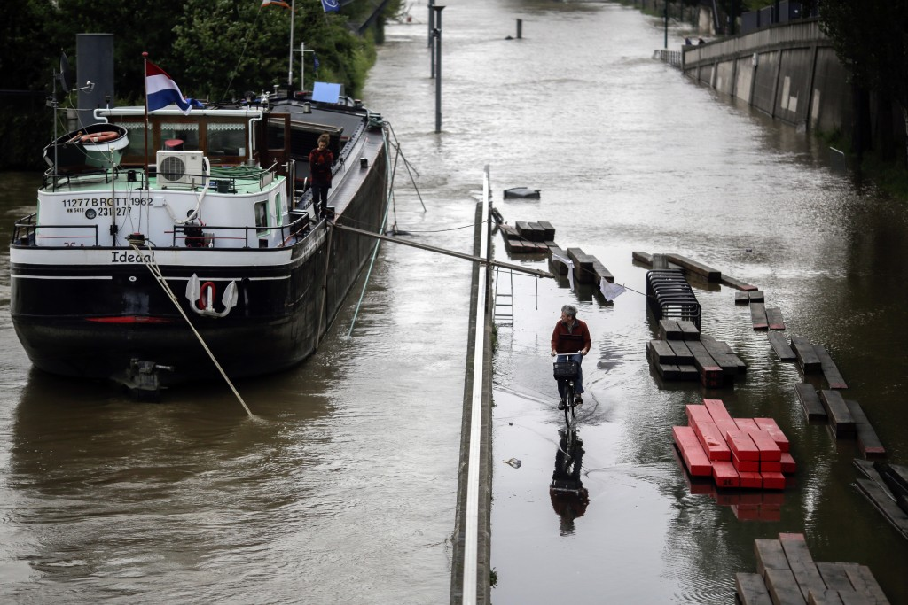 A man rides a bike through a road by the overflowing river Seine in Paris, Thursday, June 2, 2016. Floods inundating parts of France and Germany as rivers have broken their banks from Paris to Bavaria. (AP Photo/Markus Schreiber)