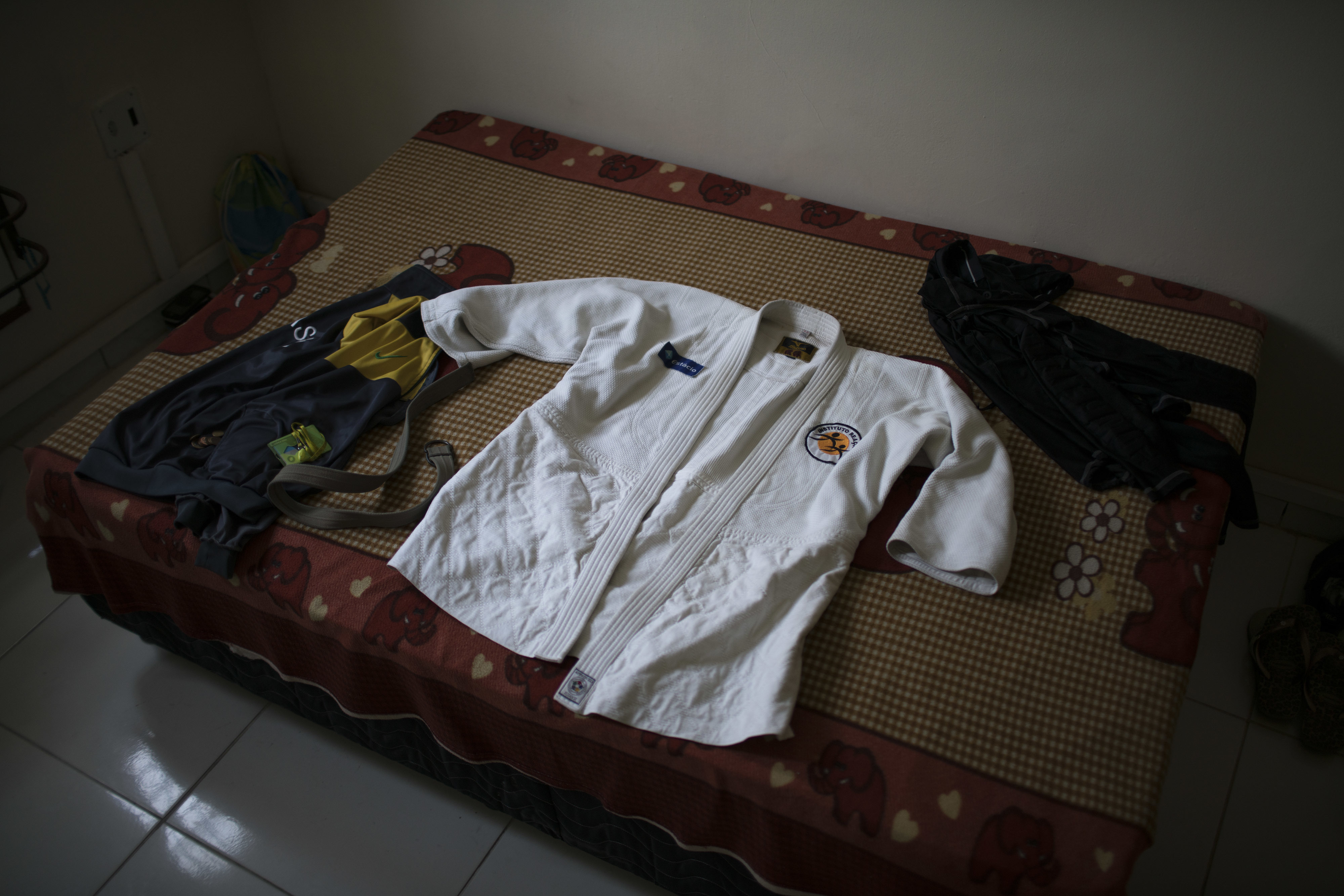 In this May 28, 2016 photo, the judo gi of Yolande Mabika, a refugee from the Democratic Republic of Congo, sits on her bed after she cleaned it at her newly rented apartment in Rio de Janeiro, Brazil. Mabika is hopeful that she will be part of the first ever team competing in the Olympic Games under the Olympic flag, instead of any one country. This week, the two hopefuls will find out whether they made the cut. (AP Photo/Felipe Dana)