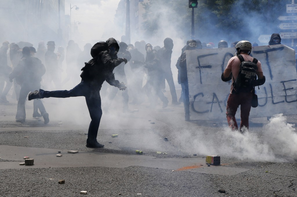 Youth throws objects while clashing with police forces during a demonstration in Paris Tuesday, June 14, 2016. Protesters in Paris threw projectiles at police officers, who responded with tear gas, amid demonstrations by tens of thousands of people opposed to a proposed labor law. (AP Photo/Francois Mori)