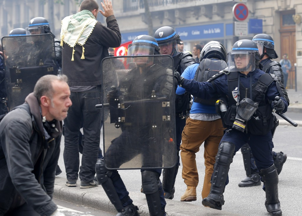 Riot police officers take position during a demonstration in Paris Tuesday, June 14, 2016. Protesters in Paris threw projectiles at police officers, who responded with tear gas, amid demonstrations by tens of thousands of people opposed to a proposed labor law. (AP Photo/Francois Mori)