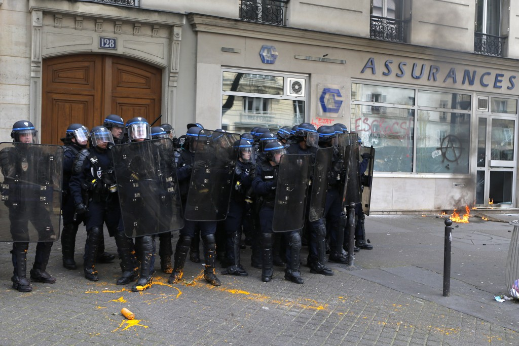 Riot police officers take position during a demonstration in Paris, Tuesday, June 14, 2016. Street protests are planned across France, rail workers and taxi drivers are going on strike and the Eiffel Tower is due to be closed as part of a protest against a reform aimed at loosening the country's labor rules. (AP Photo/Francois Mori)