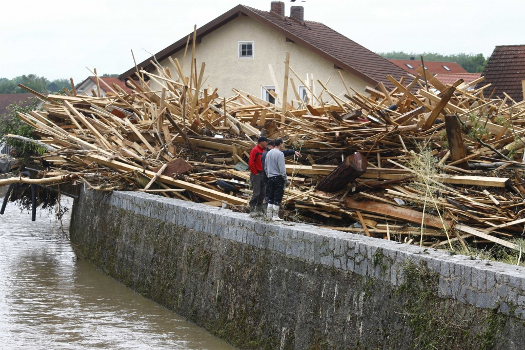 People stand besides wooden blocks in Simbach am Inn, Germany, Thursday, June 2, 2016. Several people have died in the flooding, which swept through the towns of Simbach am Inn and Triftern, while others have been reported missing. The waters have receded, and disaster relief crews were on the scene helping to clear the wreckage, while helping to prepare for more possible flooding. There are warnings of more storms in the forecast. (AP Photo/Matthias Schrader)