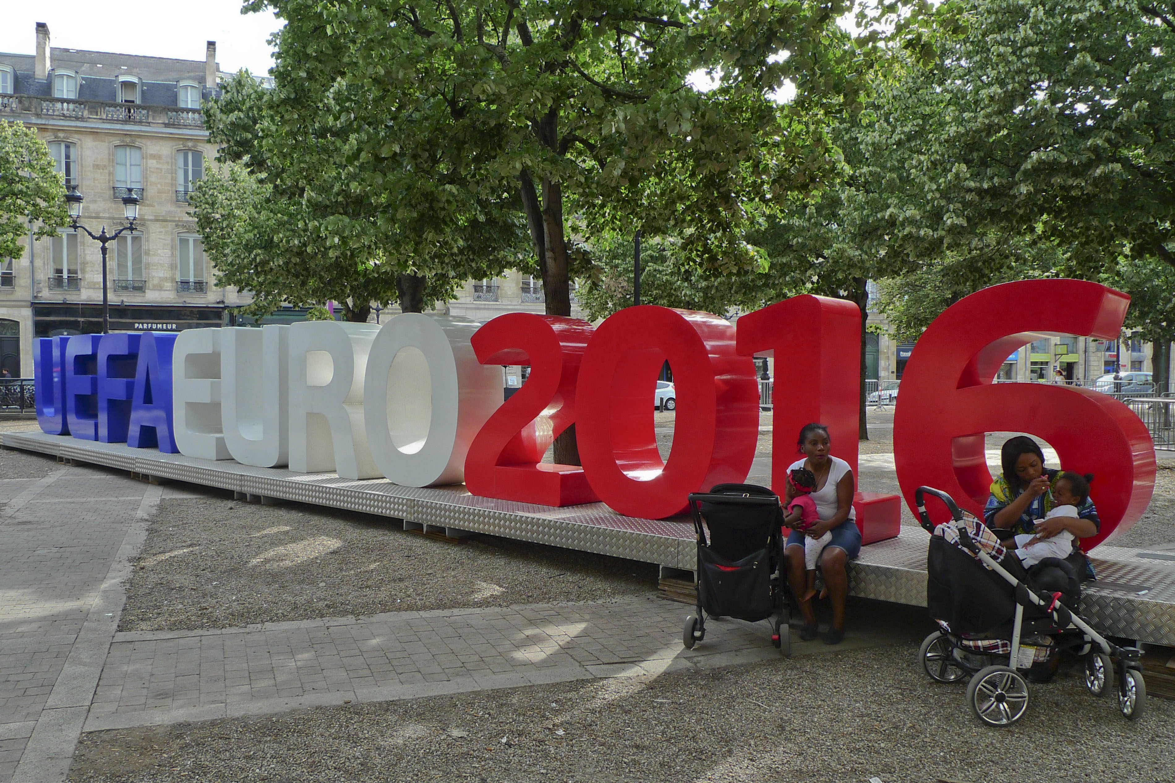 Two women sit with their babies in front of a Uefa Euro 2016 installation, in Bordeaux, France, Thursday, June 9, 2016. The Euro 2016 Soccer Championship starts with the opening match on Friday, June10, 2016 in Paris. (AP Photo/Andrew Medichini)