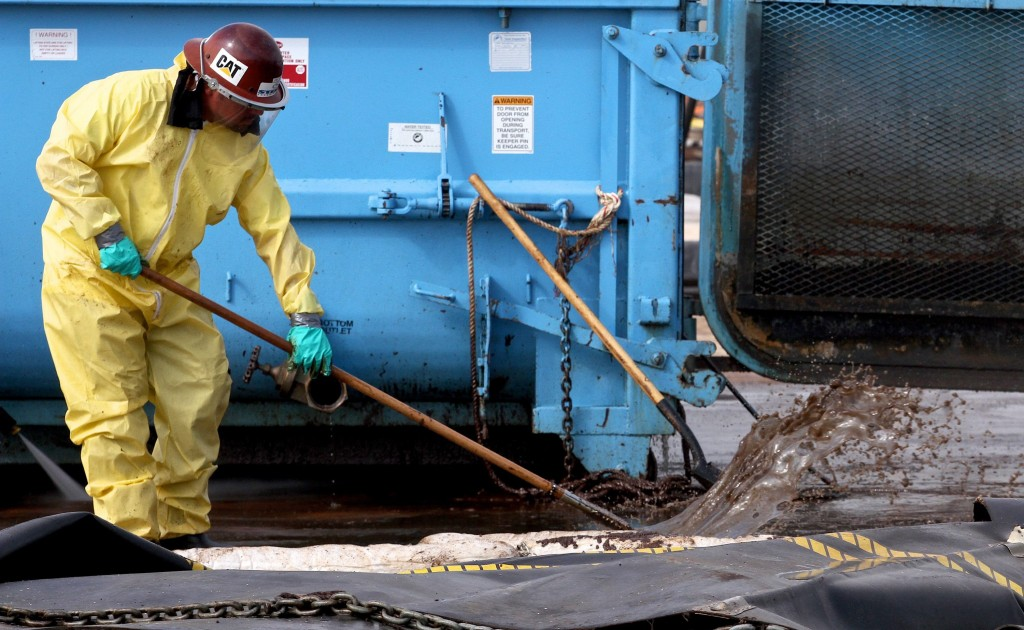 epa02250539 A worker with Patriot, a company contracted with BP, cleans oil sludge after decontaminating used boom from the Deepwater Horizon Oil Spill response at a facility in Theodore, Alabama, USA on 16 July 2010. According to officials, the facility has repaired and redeployed over 25 miles of boom since the response began. The BP Deepwater Horizon oil spill, which began almost 3 months ago, is the largest in US history and continues to threaten wildlife, the ecosystem and the economy of the Gulf Coast as BP and government officials attempt to stop the flow and remove what has already been released. EPA/DAN ANDERSON