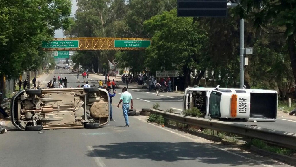 epa05378457 A general view shows overturned police vechicles, which were attacked by teachers during a protest against the education reform in the country, in Oaxaca, Mexico, 19 June 2016. At least three people died and 45 got injured in the clashes that began on the Oaxaca-Puebla federal road as authorities tried to end a block, started by the protesting teachers. EPA/STR