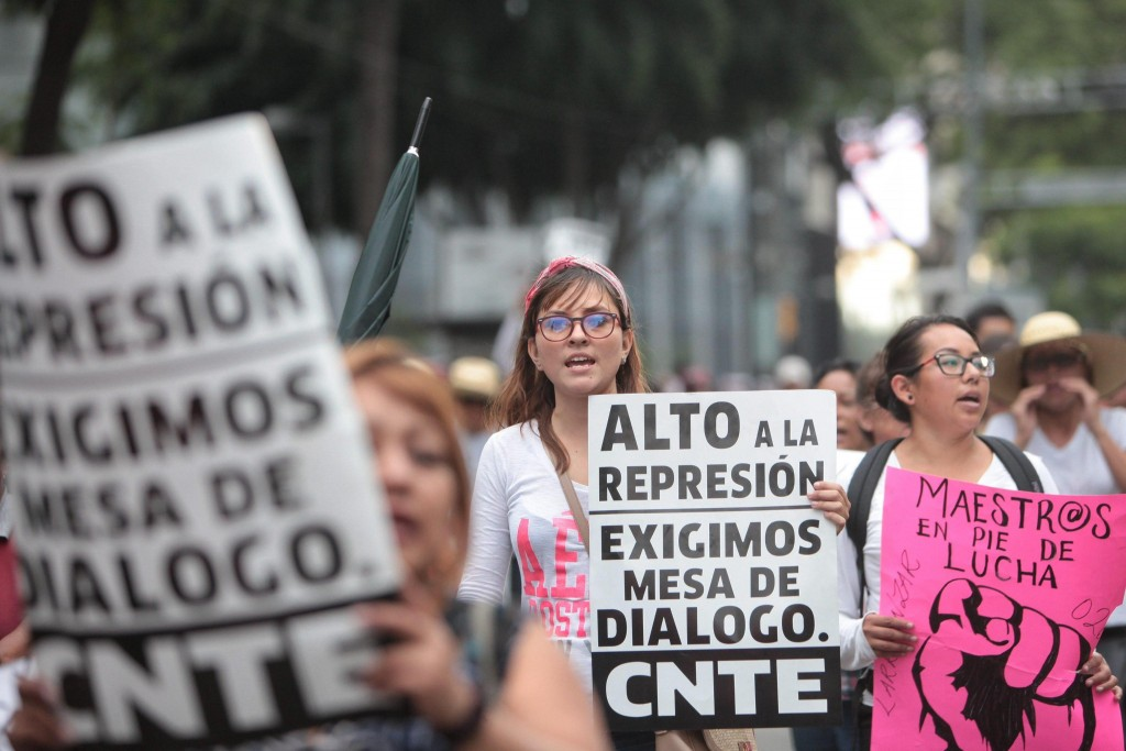 epa05374177 Members of the National Coordination of Education Workers (CNTE) teachers' union hold banners as they march in Mexico City, Mexico, 17 June 2016. Members of the CNTE, coming from the Mexican states of Guerrero, Chiapas, Oaxaca, and Michoacan, protested against the education reform and called for resuming negotiations with authorities. Banner reading 'End The Repression. We Demand Roundtable Talks. CNTE'. EPA/SASHENKA GUTIERREZ