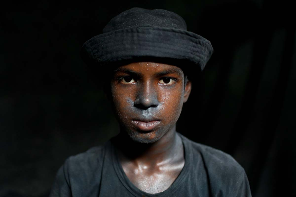 Bangladeshi boy Imran, 11, looks towards camera as he works at a factory that makes metal utensils in Dhaka, Bangladesh, Sunday, June 12, 2016. He earns less than $5 per day. The World Day Against Child Labor, which was initiated in 2002 by the International Labor Organization to highlight the plight of child laborers, is observed across the world on June 12. (AP Photo/ A.M. Ahad)