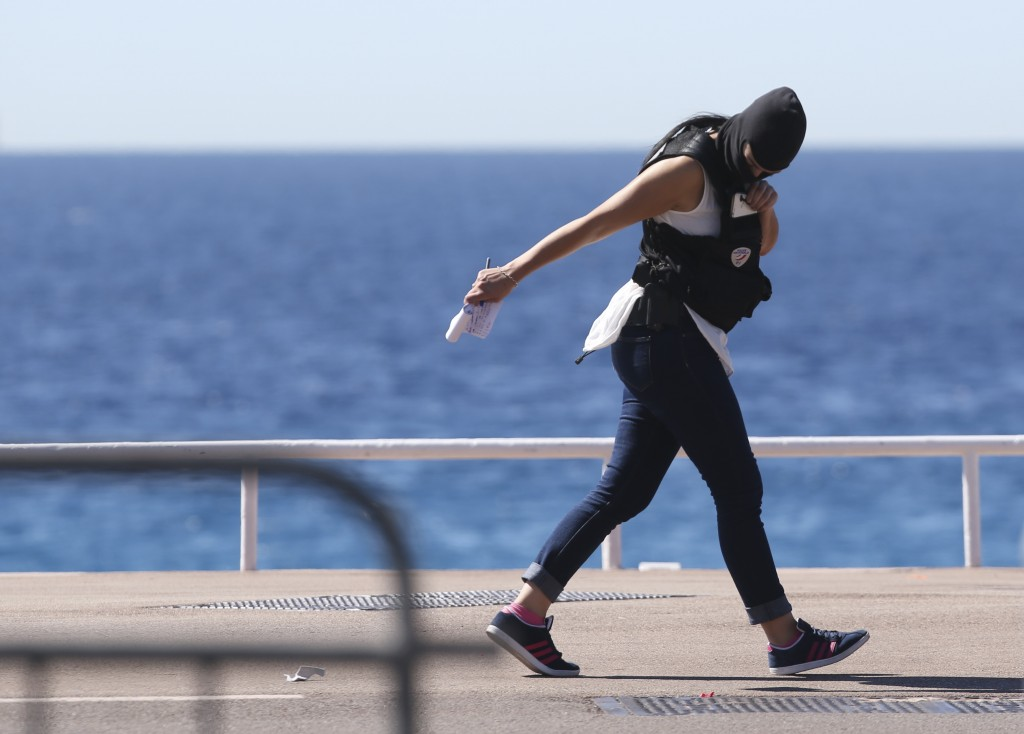 A forensic police woman walks at the scene of an attack after a truck plowed through a crowd in Nice, southern France, Friday, July 15, 2016. A large truck plowed through revelers gathered for Bastille Day fireworks in Nice, killing more than 80 people and sending others fleeing into the sea as it bore down for more than a mile along the Riviera city's famed waterfront promenade. (AP Photo/Luca Bruno)