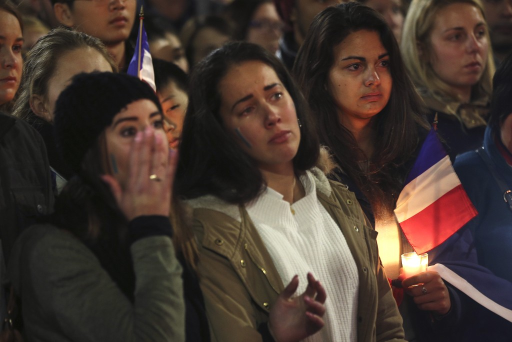 A young woman wipes her face as people honor victims of the Bastille Day attack with a moment of silence during a vigil, in Sydney, Australia, Friday, July 15, 2016. World leaders are expressing dismay, sadness and solidarity with France over the attack carried out by a man who drove truck into crowds of people celebrating France's national day in Nice. AP Photo/Rob Griffith)