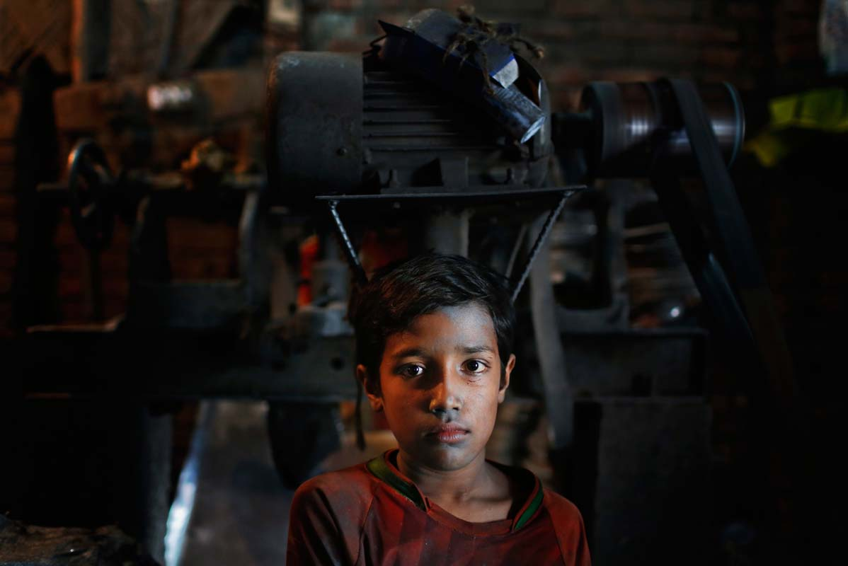 Bangladeshi boy Robin,10, looks towards camera as he works at a factory that makes metal utensils in Dhaka, Bangladesh, Sunday, June 12, 2016. He earns less than $5 per day. The World Day Against Child Labor, which was initiated in 2002 by the International Labor Organization to highlight the plight of child laborers, is observed across the world on June 12. (AP Photo/ A.M. Ahad)