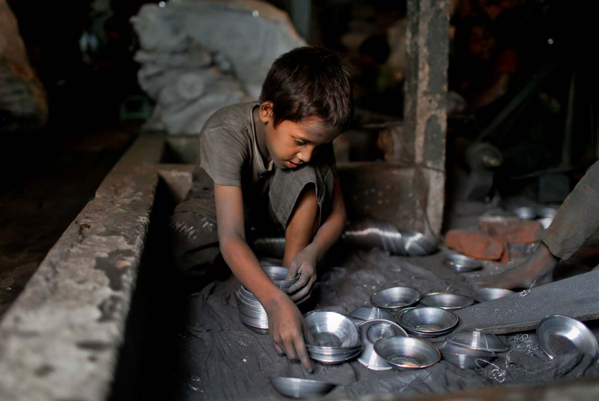 In this Sunday, June 12, 2016, photo, Ridoy, 7, works at a factory that makes metal utensils in Dhaka, Bangladesh. The World Day Against Child Labor, which was initiated in 2002 by the International Labor Organization to highlight the plight of child laborers, is observed across the world on June 12. (AP Photo/A.M. Ahad)