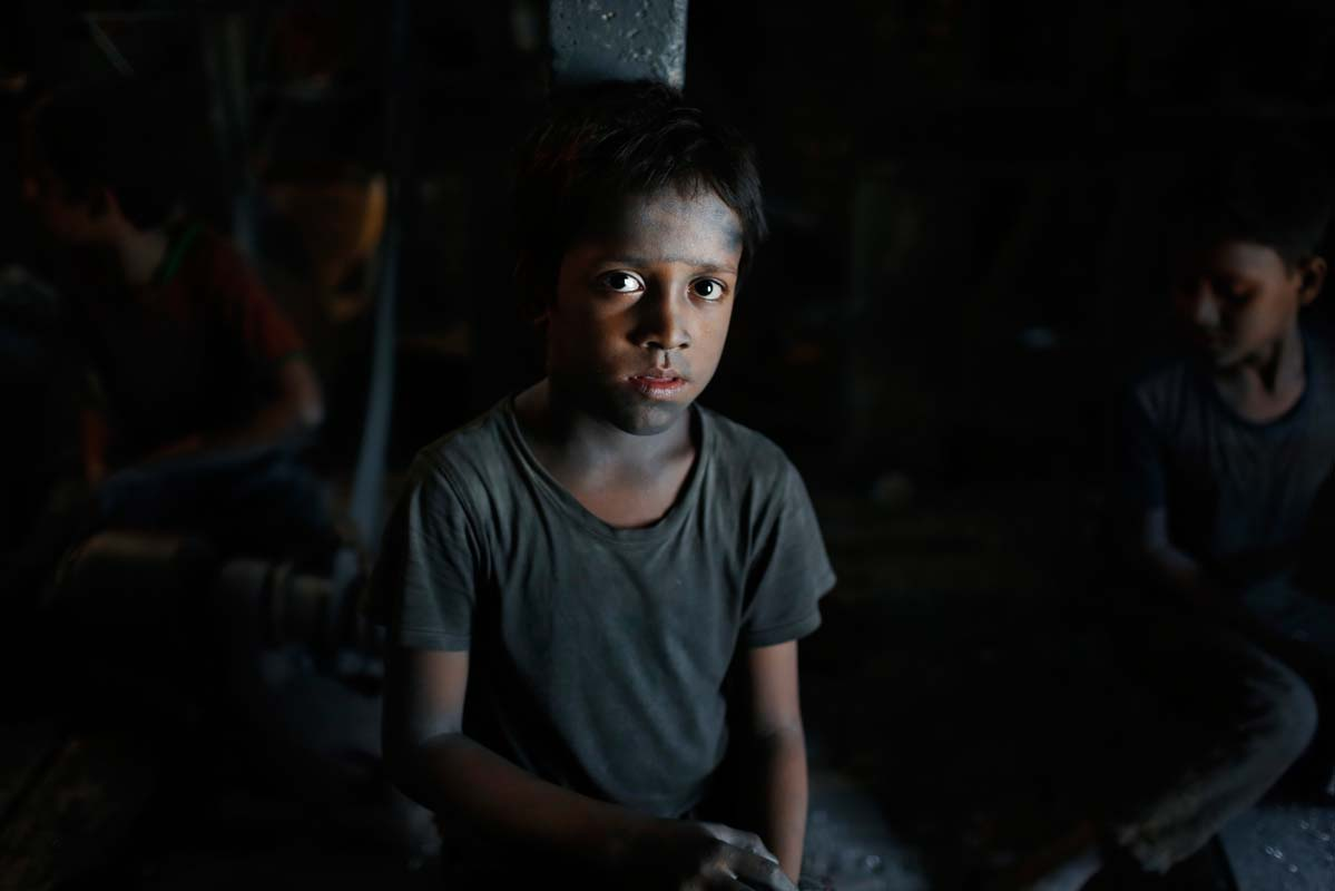 Bangladeshi child Ridoy, 7, looks towards camera as he works at a factory that makes metal utensils in Dhaka, Bangladesh, Sunday, June 12, 2016. He earns less than $5 per day. The World Day Against Child Labor, which was initiated in 2002 by the International Labor Organization to highlight the plight of child laborers, is observed across the world on June 12. (AP Photo/ A.M. Ahad)