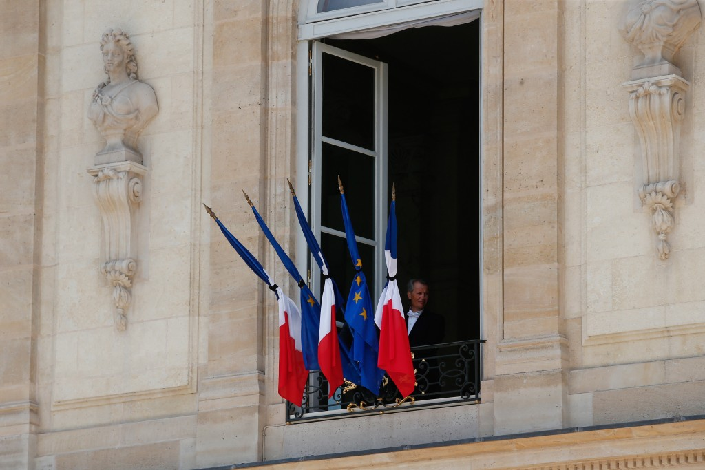 A man stands next to a half staff French flags, at the Elysee palace in Paris, Friday, July 15, 2016. French Prime Minister Manuel Valls said the government is declaring three days of national mourning after the attack in Nice that left at least 84 people dead. Speaking after an emergency meeting, Valls said the national mourning would begin Saturday. (AP Photo/Thibault Camus)