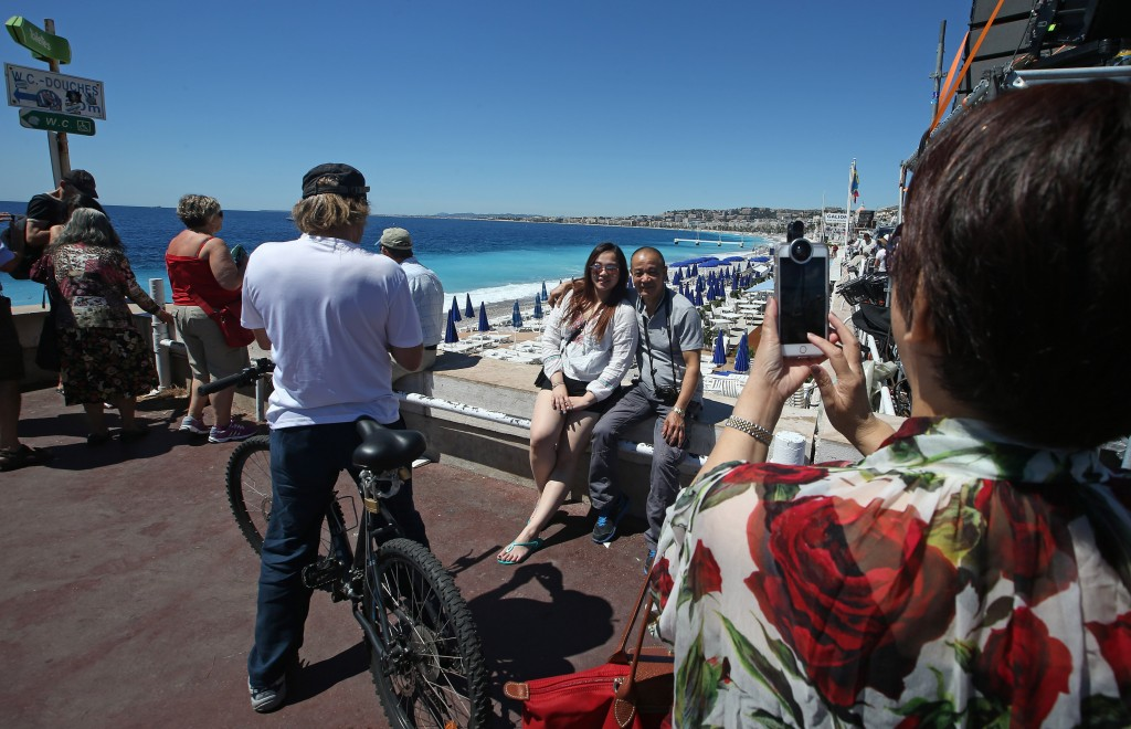 People have their photo taken overlooking the beach and not far from the site of the truck attack in the French resort city of Nice, southern France, Friday, July 15, 2016. France has been stunned again as a large white truck killed many people after it mowed through a crowd of revelers gathered for a Bastille Day fireworks display in the Riviera city of Nice. (AP Photo/Luca Bruno)