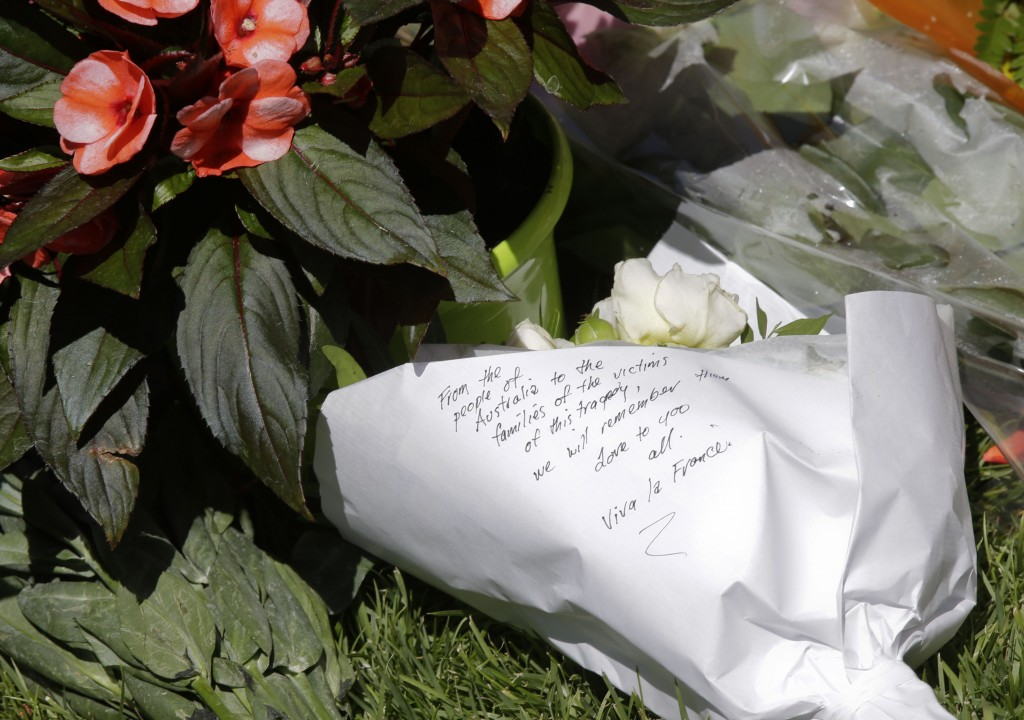 Flowers are placed near the scene of an attack after a truck plowed through a crowd in Nice, southern France, Friday, July 15, 2016. A large truck plowed through revelers gathered for Bastille Day fireworks in Nice, killing more than 80 people and sending others fleeing into the sea as it bore down for more than a mile along the Riviera city's famed waterfront promenade. (AP Photo/Luca Bruno)